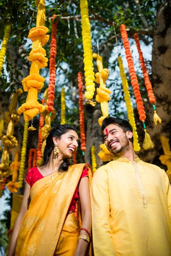 Genda phool decor for haldi with couple in yellow