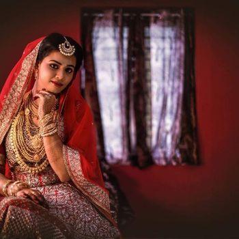 Pretty bridal portrait at home in a red bridal lehenga