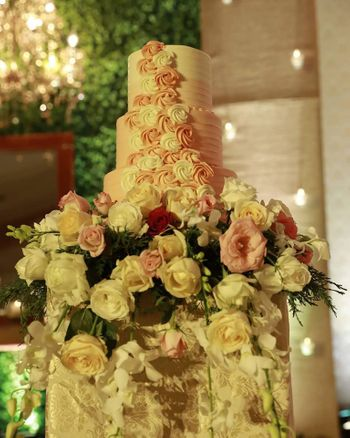 Photo of A three-tier wedding cake with elegant floral decor