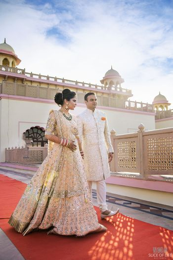 A bride and groom in coordinated ivory outfits