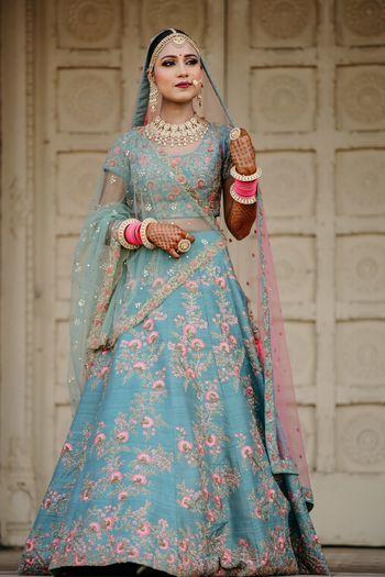 A bride in a blue lehenga with pink chooda