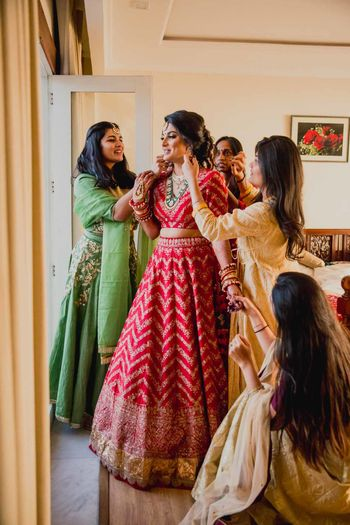 Bridesmaids help a bride in red get ready