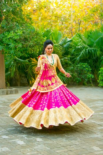 Bride twirling in gold and pink lehenga with broad border