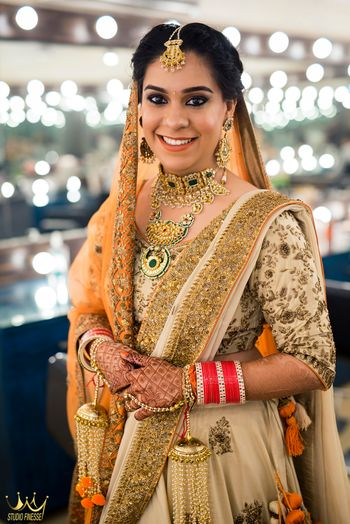 Orange and gold bridal look with orange kaleere and green jewellery