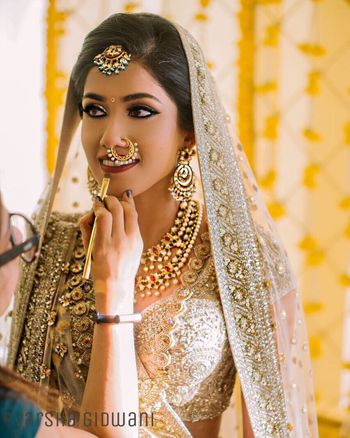 Bold bridal eye makeup with beige lehenga