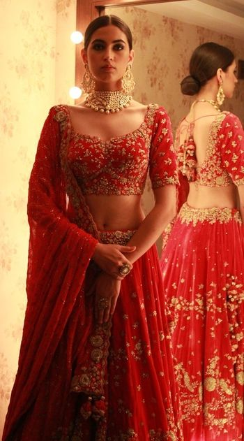 Photo of Crimson Red and gold bridal lehenga by Dolly J