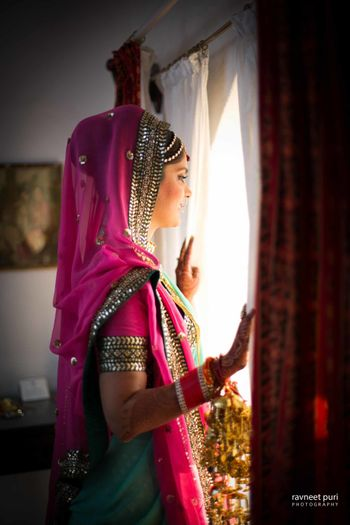 Bride in green and pink bridal lehenga looking out of window