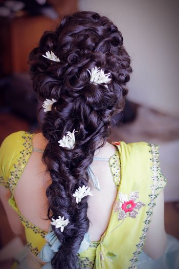 Twisty braid hairstyle with flowers for mehendi