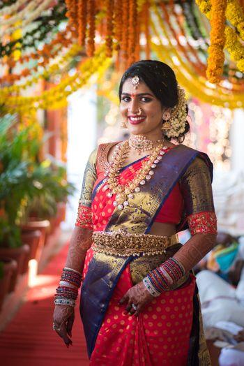 South Indian bride in orange and purple saree