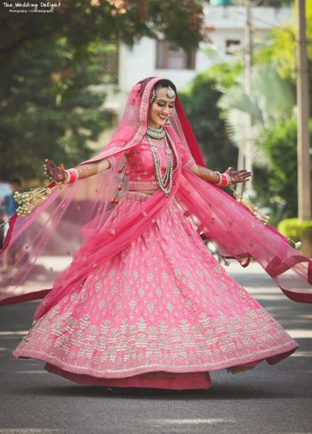 Photo of Sikh bride in bright pink lehenga twirling