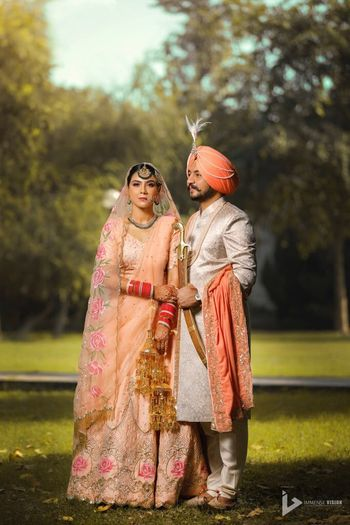 Photo of Matching bride and groom Sikh couple in peach