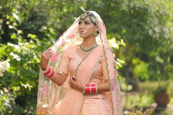Peach bridal lehenga with green jewellery