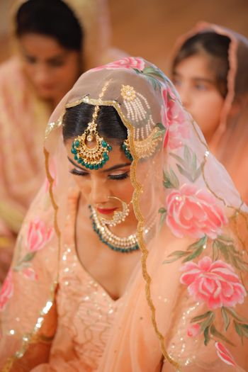 Photo of Bride in peach lehenga and printed dupatta