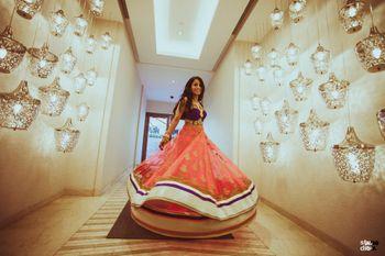 Photo of Bride twirling in orange layered lehenga