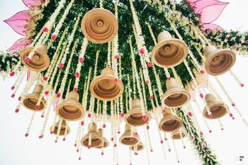 Photo of Unique mandap decor with hanging temple bells and floral strings