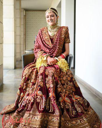 Bride dressed in a regal lehenga with peacock motifs.