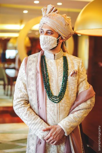 Groom in beige embroidered sherwani with matching face mask