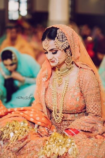 A bride in orange lehenga and gold jewellery at her Anand Karaj