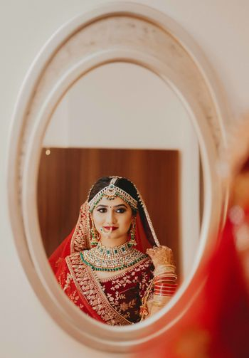 Photo of North indian bridal portrait looking into mirror