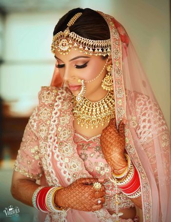 A bridal shot in baby pink lehenga