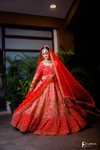 A stunning bride twirling in her beautiful red lehenga.
