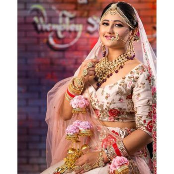A happy bride in a lovely light pink lehenga with floral embroidery.