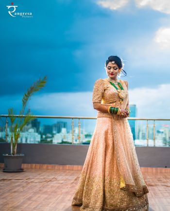 Shimmery gold lehenga with sequins and green jewellery