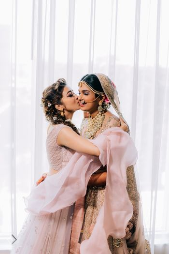 Photo of A cute bride and sister moment on her wedding.