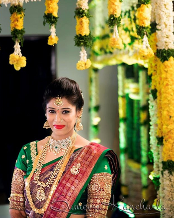 A bride in a green and red kanjeevaram with temple jewellery