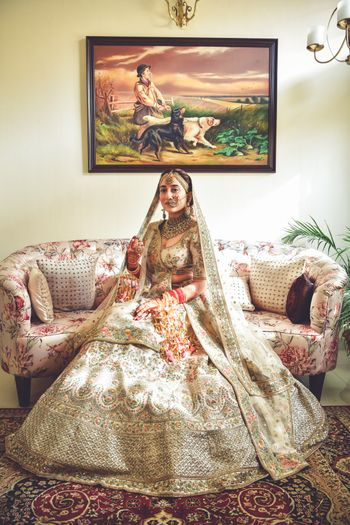 A regal Sikh bride in ivory lehenga on her wedding day.