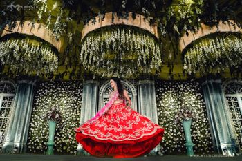 Photo of bride twirling on stage in her red and pink lehenga