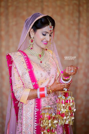 Sikh bride in peach wearing kaleere with pompoms