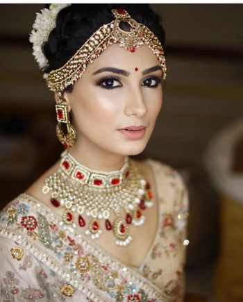 A bride all decked up with red and gold jewelery and nude makeup
