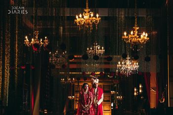 wedding decor idea with couple standing under chandeliers