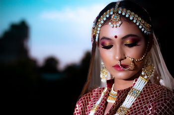 A bride in maroon lehenga and pearl jewelry