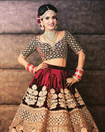 A bride in a maroon lehenga poses for the camera