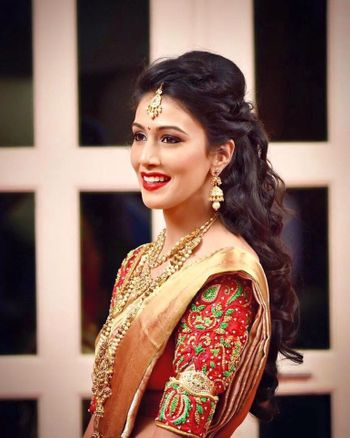 South Indian bride with open hair and embroidered blouse