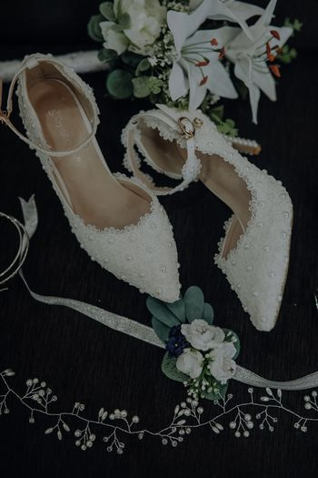 Photo of Bridal Footwear with lacey pattern and pearl embellishments.