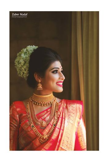 Photo of A south Indian bride in red kanjeevaram with temple jewelry and gajra in her hair
