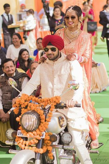 A sikh bride and groom enter the wedding venue on a bike