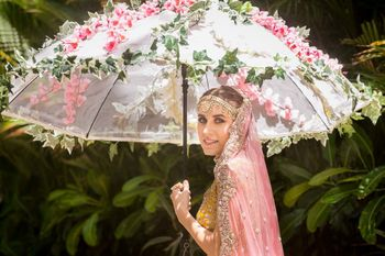Photo of Bride entering under floral umbrella with pink and greens
