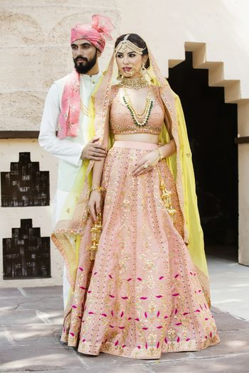 Photo of A bride and groom coordinate in white and pink on their wedding day