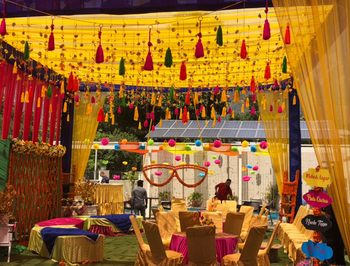 Colorful mehendi decor with hanging tassels and sunglasses
