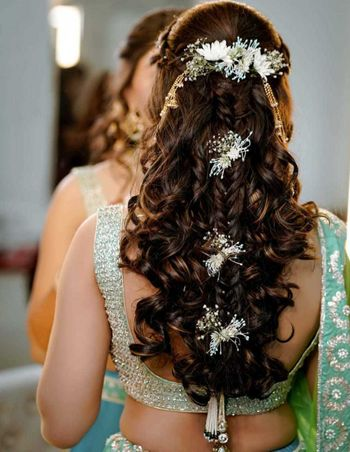 Half tied hairdo with soft curls, some braids, and flowers.