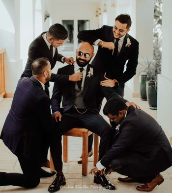 Photo of groom with his groomsmen getting ready shot