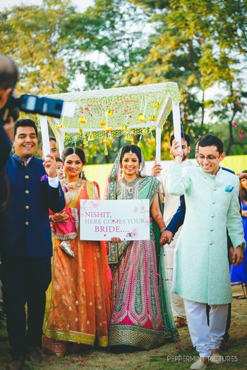 Photo of Bridal entry idea under phoolon ka chadar with sign