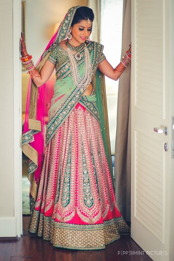 Photo of Bride in mint and bright pink bridal lehnega