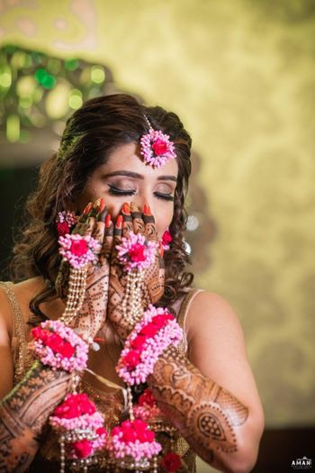 A bride-to-be flaunting her floral hathphool on her mehendi day