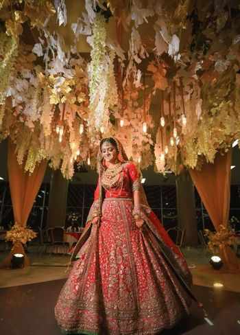 A bride in red poses under a ceiling of flowers