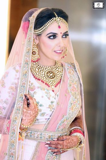 Pretty bride in pastel pink lehenga with gold jewellery